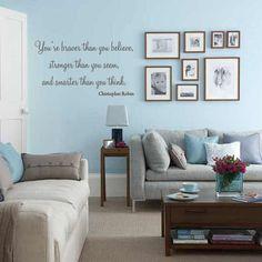 sala azul com sofá cinza e adesivo de frase