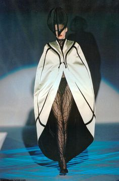 Diana Garter wears a cocoon cape of pale green satin lined with black velvet over a 'Dragonfly' bodystocking in black flocked net with a 'Fly' hat in black velvet and horsehair. Les Insectes Couture Collection SS 1997 Thierry Mugler: Galaxy Glamour