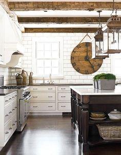 Oversized subway tile backsplash, exposed wood beams, white cabinets, furniture style islands.