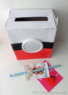 Recycled Pokeball Valentine Box - DIY Adulation - - This recycled Pokeball Valentine box is made from items you already have laying around. Whip it up in time for your child's party. Pokemon Valentines Box, Homemade Valentine Boxes, Valentine Boxes For School, Valentines For Boys, Valentines Day Party, Valentine Day Crafts, Valentine Ideas, Printable Valentine, Valentine Wreath