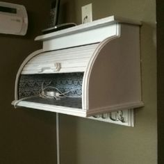 Re-purpose breadbox as a shelf. Painted white, lined with scrapbook paper, mounted to the wall.