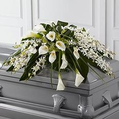 The FTD® Angel Wings™ Casket Spray is an exceptionally gorgeous way to bring peace and beauty to their final farewell service. White Dendrobium orchids, white calla lilies, green hydrangea and a variety of lush greens are artfully. Casket Flowers, Grave Flowers, Cemetery Flowers, Send Flowers, Funeral Bouquet, Funeral Flowers, Wedding Flowers, Arrangements Funéraires, Funeral Floral Arrangements