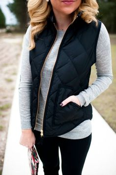 Navy quilted vest over gray top and black jeans.