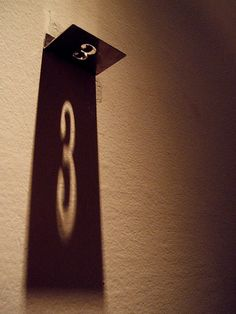 Such creative signage. The light from above casts a shadow to display the number on the wall.