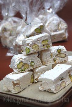 Nougat blanc au miel - 2 blancs d'oeufs ; 1 pincée de sel ; 150 ml d'eau ; 120 ml (175 g ) de miel ; 2 et 1/2 tasses ( 500 g ) de sucre ; 1 cuillère à table de vanille liquide ; 1 tasse (150 g ) de pistaches et d'amandes non blanchies ( en quantité égales ), torréfiées
