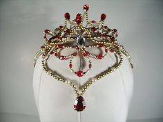Stunning hand made headpiece with golden frame and red ruby stones and crystals, white pearls, central drop and sides. Entirely hand crafted. Exclusively distributed by Dancewear by Patricia. Delivery