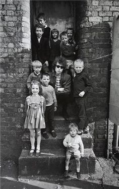 Bob Dylan sits with children in Liverpool, England, 1966. Photograph by Barry Feinstein