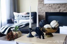 Black candlesticks, mini pumpkins, and frosted pinecones creates a spooky Halloween coffee table.