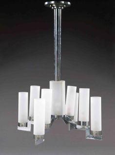 Jacques Adnet Grand lustre moderniste en métal chromé présentant un fût central cylindrique animé à la base d'une lumière protégée par un cylindre en verre dépoli, accueillant quatre bras de lumière à gradins présentant chacun deux lumières. abat-jour cylindriques en verre dépoli. haut. 91 cm - larg. 65 cm