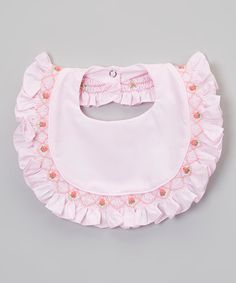 Catch stray spills and dribbles with this smocked bib. Comfortably secured using a snap closure and made from an absorbent cotton blend, it's a must-have for mealtime.