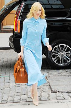 Cate Blanchett wears a light blue button-down shirt dress with nude heels and a tote bag