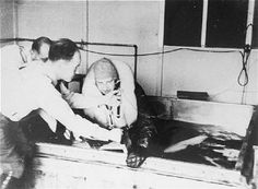 """""""A victim of Nazi medical experiments is immersed in icy water at the Dachau concentration camp. SS Doctor Sigmund Rascher oversees the experiment."""""""