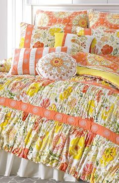 Peach ribbon trims the ruched floral cotton of a spring-fresh cotton comforter that reverses to a sunny yellow print.