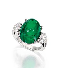 PLATINUM, EMERALD AND DIAMOND RING.  Centered by an oval-shaped cabochon emerald weighing 15.22 carats, flanked by two oval-shaped diamonds weighing .74 and .73 carats, respectively, size 6¼.