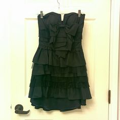 BeBe LBD Fun and girly bebe dress worn only once! Great condition! A bow detailing on the front , strapless.with a slit and lace and ruffles! bebe Dresses