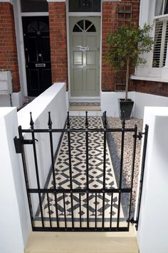 Plastered rendered front garden wall painted white metal wrought iron rail and gate victorian mosaic tile path in black and white scottish pebbles York stone balham london Victorian Front Garden, Victorian Gardens, Victorian Terrace, Victorian Homes, Up House, House Front, Terrace House Exterior, Front Path, Gardens