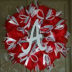 "This is a Alabama Crimson Tide deco mesh 24"" wreath made with red and white mesh and accented in houndstooth ribbons and a houndstooth script A. ALL custom wreaths and hand painted glassware ships in"