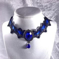 "Victorian Gothic Lace Black & Blue Jewel Choker 16"" long including extender, thickness 1.5"". Crocheted material and blue satin ribbon choker with statement jewelry faceted blue costume jewel in center. You can save the most by bundling. I offer a 20% discount on all bundles of just 2 or more items. I accept reasonable offers. Most items listed I only have the one so hurry and grab if you're interested. Please ask any questions. Boutique Jewelry Necklaces"