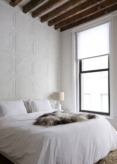 white bedroom, fur throw, wood beams, white wall detail