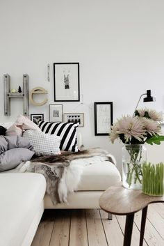 love the black and white stripe pillow, white couches, and gallery wall