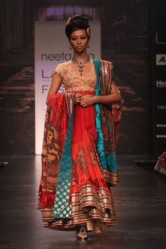 Rust  georgette ghagra with kalamkari patchwork and a asymmetric lace and net blouse with a shaed green and rust dupatta with kalamkari motifs.