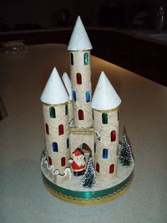 Vintage Mica Putz Cardboard Christmas Castle with Santa and trees. (lorrainesfavoritefinds/eBay)