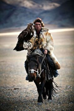 A mongolian hunter on a riding horse armed with a Golden Eagle, West Mongolia. by Viacheslav Smilyk photographer