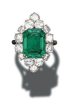 EMERALD AND DIAMOND CLUSTER RING, BY CARTIER. Set with a rectangular-cut emerald weighing 7.23 carats in a circular-cut diamond navette-shaped surround to the 18K gold hoop