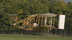 A replica Wright brothers plane flies low to the ground with trees in the background Dayton Aviation Heritage National Historical Park Ohio