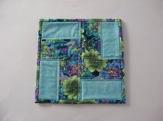 This is a colorful set of 2 snack mats/mug rugs. The set features 2 mats in bright floral fabrics, featuring the colors of blue, aqua, green, lavender, pink and cream. Each mat is 8 square and has been created in a strip pieced rail fence pattern. Mats are backed with a tone on tone cream leafy vine print fabric. Quilting has been done in an off white thread, front and back. Binding on each mat is handmade from the floral print fabric used in the mat front, machine sewn to the front and hand…