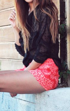 sheer dotted blouse with bright shorts.