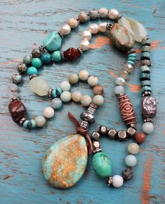 Luxury redefined! This long, hand-knotted bohemian necklace features a variety of semi-precious gemstones in neutral colors--turquoise, pale green, brown and silver--and a stunning Turquoise pendant.  Slips effortlessly over your head. Wear it with denim, a lacy peasant top, a mustard cardi for a cool boho chic vibe...neutral colors are easy to match.