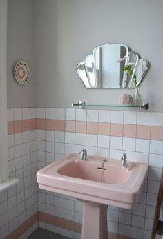 salle de bain rose et blanche avec carrelage mural, lavabo et miroir éventail vintage