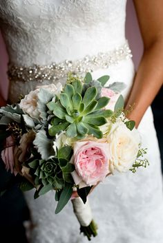 Soft pinks and muted greens add some colour to this elegant ivory bouquet.