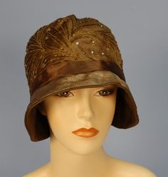 TWO METALLIC CLOCHES, 1920's. One bronze satin with stylized plumes in gold metallic thread decorated with rhinestones and bugle beads, narrow gold lame brim with brown satin band, (band unstitched, no lining). One with two silver rounds flanked by flame forms on an allover ground of coiled gold squiggles on net with fold back brim, (no lining, brim partially unstitched). Together with net beret having brown velvet band and beaded floral decoration. Front Detail