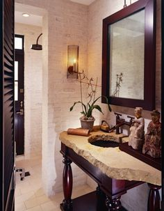 love the modern mirror, contrasting colors, natural stone, buddha statues