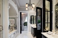 Windowed black French doors to bathroom and arched ceiling around bathtub