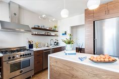 Becky and Sarah skipped an upper line of cabinets on the most visible wall and went with slim open shelving made from recycled wood in their Clinton Hill kitchen.