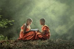 Young Buddhist monk reading outdoors, sitting outside The temple,Sakonnakhon,Thailand.