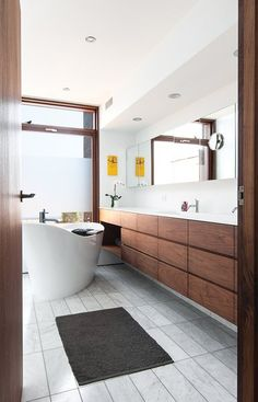 Modern home with Bath Room, Freestanding Tub, Marble Floor, and Marble Counter. The bathtub faces a Spanish-cedar-framed window overlooking the back deck. Once the outside plants have grown up enough to provide privacy, the adhesive film on the window will be removed. Photo of A Toronto Tudor Becomes Bright, Luxurious Home
