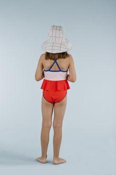Bañador para niña, de algodón Pima y elastano, de tinycottons. Correas azules cruzadas en la espalda. Volante en la cintura. Protección UV.