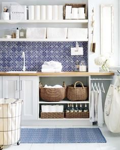 Pretty blue and white tiles, crisp whites, and natural baskets liven up a laundry room.