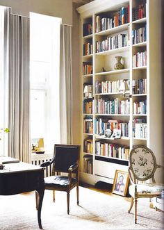black Louis XIV chair, tall curtains, and bookcase // office design