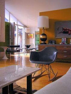 Mod. Deep mustard yellow, a classic midcentury hue, perfectly complements the retro attitude of this living area and reflects the golden flooring color.