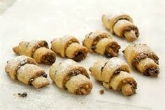 "RUGELACH-1 c butter creamed with 8 oz cream cheese, add 2 c flour until a dough forms; roll into a ball and chill 1 hour. Combine 3/4c chopped toasted almonds, 1/2c sugar, 1/2c currants, 2 tbsp honey & 1 tsp cinnamon. Divide dough in 4, roll each into circle 1/16"" thick, cut each into 8 wedges. Spoon 1 tbsp filling down centre of each & roll. Place on parchment lined cookie sheet. brush tops with cream and sprinkle with sugar. Bake at 350F for 15-20 min until golden brown."