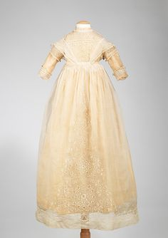 1840–60: French; cotton, silk. Length at CB 37 in.  Christening ceremonies were elaborate affairs. This infant's dress is a particularly beautiful example with fine embroidery and detail work, such as the pintucking at the bodice. It is unusual to have a non-washable fabric, such as silk, as the lining for a child's dress, which shows the wearer was a member of a prominent family.
