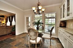 Traditional Dining Room with High ceiling, Built-in bookshelf, slate tile floors, Stone Locator Durango Cream Beveled 4x4