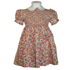 """Emily (Pink & Blue) - Traditional smocked dress. Short puff sleeves and white """"Peter Pan"""" collar piped in matching floral fabric. Button up back with tie back belt in same floral fabric. Available in sizes 6 months - 8 years."""