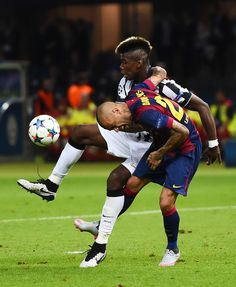 Paul Pogba of Juventus is tackled by Daniel Alves of Barcelona during the UEFA Champions League Final between Juventus and FC Barcelona at Olympiastadion on June 6, 2015 in Berlin, Germany.