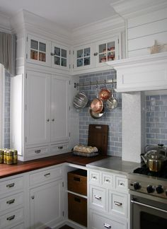 #cultivateIt  Love the eclectic look, and the use of the pot rack/display in what would otherwise be a wasted space.  The use of countertop drawers creates storage in an awkward space and visually connects the tall cabinet with the hearth/hood.        Coastal Kitchen III (Cultivate.com)